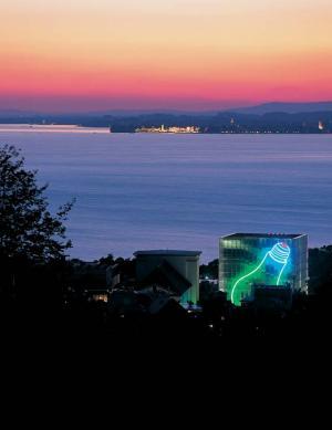 Foto: KUB - Kunsthaus Bregenz mit Lichtinstallation und im Hintergrund die Lindauer Insel